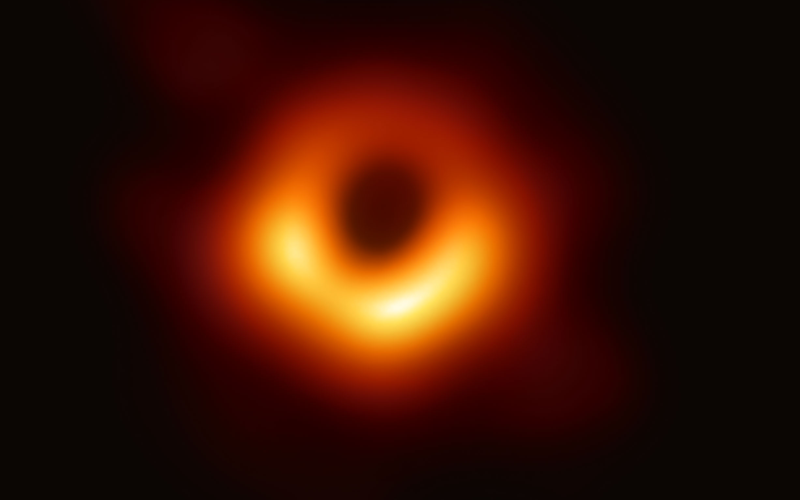 First image of a black hole. It is an orange circle in a black background.